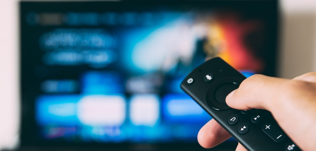 Unscharfer Fernseher im Hintergrund, Fernbedienung im Vordergrund